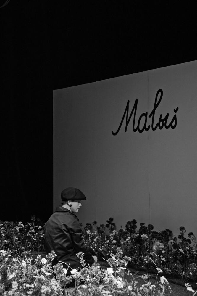Mārtiņa Kalitas Ļoņa pustumsā ar muguru pret skatītajiem sēž mākslīgo puķu klājā turpat līdzās. Foto – Justīne Grinberga